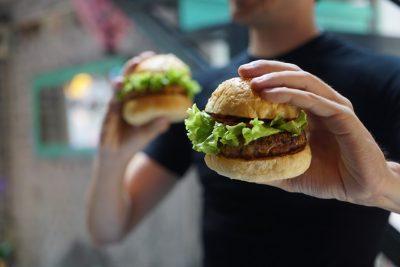 Übergewicht - Person mit zwei Burgern