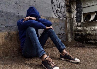 Kinderarmut - Jugendlicher sitzt am Boden und versteckt sein Gesicht